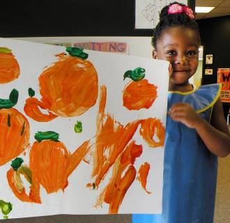 Image: Student Oluwafunto Akinnurele holds a picture of pumpkins stolen from the Child Development Center at Eastern New Mexico University in Portales