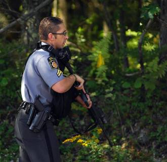 Image: A Pennsylvania State Trooper walks into a wooded area as investigators on Sunday return to scour the woods