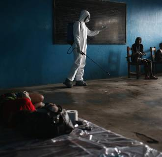 Image: A Liberian health worker speaks with families in a classroom now used as Ebola isolation ward