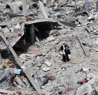 Image:A Palestinian woman walks on the rubble of destroyed houses