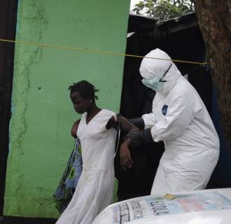 Image: Health worker brings a woman suspected of having contracted the Ebola virus to an ambulance in Monrovia