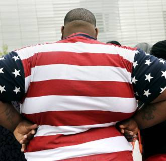 Image:overweight man wears a shirt patterned after the American flag