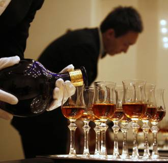 Image: A waiter is reflected in a mirror as he pours luxury Scotch whisky Royal Salute into glasses in Beijing