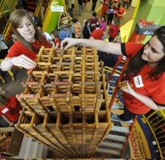 Image: Heather Hudson (left) and Hannah place logs April 2013 while setting a new Guinness World Record for the largest Lincoln Log build.  The replica of the Nebraska's state capital included 10036 Lincoln Logs and stands at 12' 4