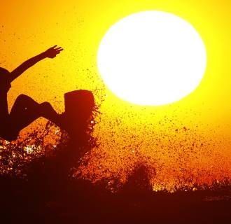 Surfer Cole Clisby rides his surfboard off the top of a wave as the sun sets off the shores of Leucadia