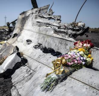Image: Flowers, left by parents of an Australian victim of the crash, laid on a piece of the Malaysia Airlines plane MH17, near the village of Hrabove
