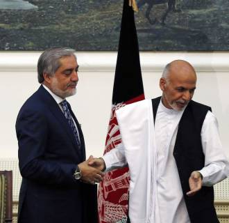 Image: Afghan rival presidential candidates Abdullah and Ghani shake hands after exchanging signed agreements for the country's unity government in Kabul