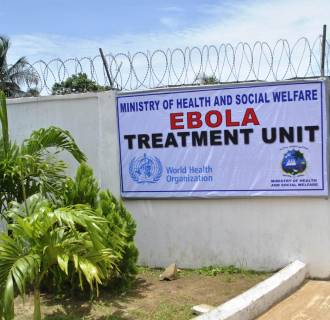 Image: A man stands at the gate of an Ebola virus treatment center in Monrovia