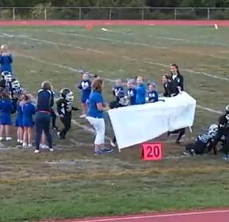 Image: Young football players have a little trouble running through a banner.
