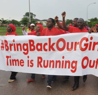 Image: People shout slogans and hold a banner during a demonstration in Abuja, Nigeria