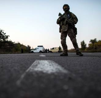 Image: A Ukrainian soldier stands guard on a road during a prisoners-of-war (POWs) exchange, north of Donetsk, eastern Ukraine