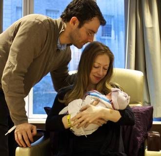 Image: Handout picture of Chelsea Clinton holding her daughter Charlotte Clinton Mezvinsky with her husband Marc Mezvinsky