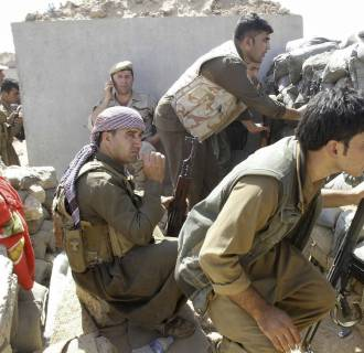Image: Volunteers with Kurdish peshmerga forces clash with Islamic State militants in the town of Daquq, south of Kirkuk