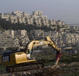 Image: A bulldozer is seen next to a new housing construction site in the Israeli settlement of Har Homa