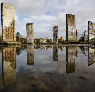 Original pieces of the Berlin Wall are mirrored in a pond as they are are displayed for sale at the city of Teltow near Berlin