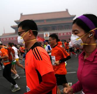 Image: Runners jog past Tiananmen Gate shrouded in haze