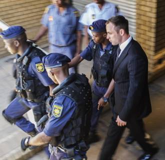 Image: Oscar Pistorius is escorted by South African policemen to a police vehicle to be transported to prison