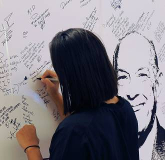 Image: A fan of Dominican-born fashion designer Oscar de la Renta leaves messages of condolence in the window of a store carrying his brand in Santo Domingo