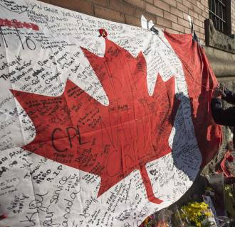 Image: People write messages on a Canadian flag in a makeshift memorial in honour of Cpl. Nathan Cirillo, outside the Lieutenant-Colonel John Weir Foote Armoury in Hamilton
