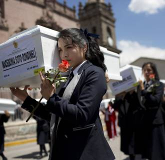 Image: A student carries a coffin containing the exhumed remains of a victim of the country's dirty war, in a procession in Huamanga, Peru