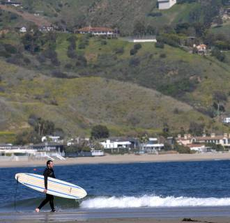 Image: A surfer heads toward the water at in Malibu