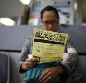 Image: Murillo reads a leaflet at a health insurance enrollment event in Cudahy, California