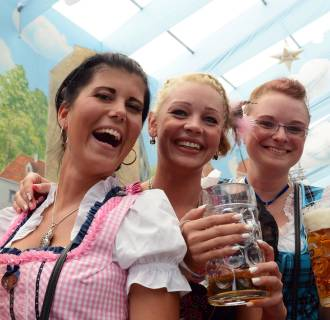 Image: Women dressed in typical Bavarian Dirndl dresses pose with beer mugs in a festival beer tent of the Oktoberfest beer festival