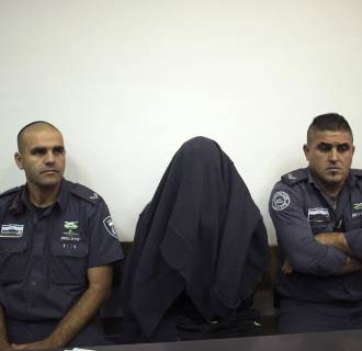 Image: Israeli prison guards sit beside a paramilitary border policeman at Jerusalem District court