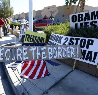 Image: Ken Adams (L) argues with an anti-Obama protester outside a high school where U.S. President Obama is scheduled to deliver remarks on his use of executive authority to relax U.S. immigration policy in Las Vegas, Nevada