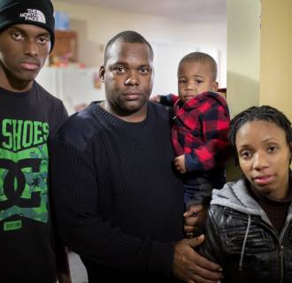 Image:Police officer Robert Howard with his two sons and wife Jamie. The family lives in Ferguson, Missouri, near the site where Michael Brown was shot and killed by police officer Darren Wilson.