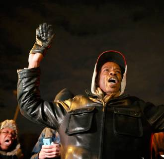 Image: A protester holds his hands in the air outside the Ferguson Police Department in Ferguson