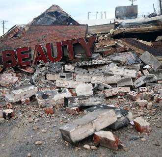 Image: A sign sits amidst rubble at a building that was damaged during a demonstration in Dellwood, Missouri