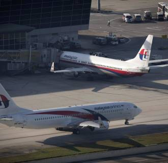 A Malaysia Airlines plane, foreground, leaves the the tarmac to take off at the Kuala Lumpur International Airport (KLIA) in Sepang, Malaysia, Friday, Nov. 28, 2014.
