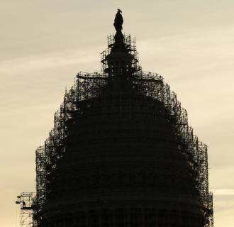 Image: A worker reaches for supplies while working atop the scaffolded dome of the U.S. Capitol in Washington