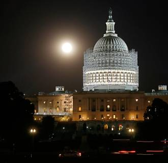 Image: The moon is seen rising behind the dome of the U.S. Capitol building, currently undergoing renovations, in Washington