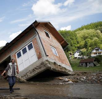 Image: A woman reacts as she walks near a house tilted by floods in the village of Krupanj, west from Belgrade