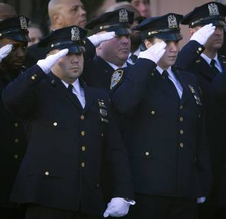 Image: Police officers salute as the casket of NYPD officer Rafael Ramos arrives for his wake at Christ Tabernacle Church in the Queens borough of New York