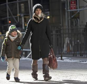 Image: A woman and a boy walk in the cold and wind past the New York Stock Exchange on Wall Street in New York