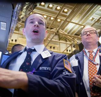 Image: Traders work on the floor of the New York Stock Exchange