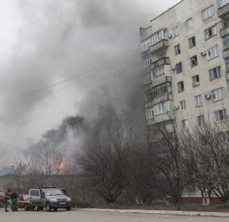 Image: Smoke and flames rise above a burning building after shelling in the eastern Ukrainian city of Mariupol, Saturday