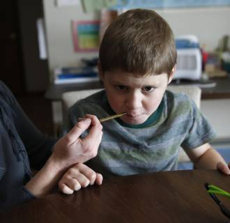 Image:  Nicole Gross uses an oral syringe to give her son Chase his daily dose of a medical marijuana oil, known as Charlotte's Web, at their home in Colorado Springs, Colo.