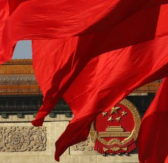 Image: The Great Hall of the People, where the Chinese Communist Party plenum is being held, is seen behinds red flags in Tiananmen square in Beijing