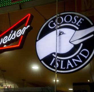 Image: A Budweiser sign is displayed along side a sign for Goose Island beer at a store in Brooklyn, New York