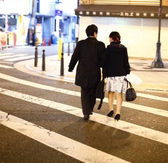 Image: Couple cross street in amusement district of Osaka