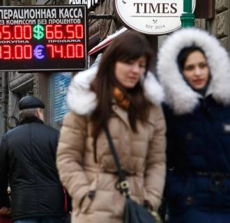 Image: People walk past a board showing currency exchange rates in Moscow