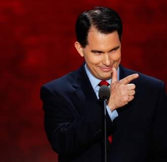 Image: Wisconisn Governor Scott Walker gestures as he addresses the second session of the Republican National Convention in Tampa