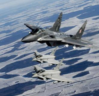 Image: A Polish Air Force MIG-29 fighter and Italian Air Force Eurofighter Typhoon fighters participate during a NATO air policing mission patrol over the Baltics from the Zokniai air base near Siauliai