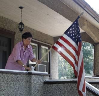 Image: Mary Kay Coyne unfurls a U.S. flag