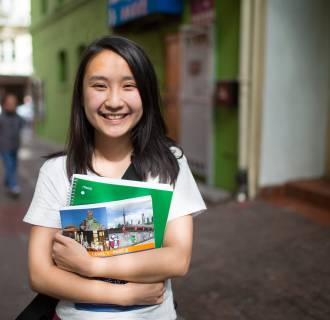 Image: Rosa Chen stands in Chinatown where she gives historical tours with the Chinatown Community Development Center.