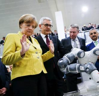 Image: German Chancellor Merkel and Indian Prime Minister Modi look at a YuMi robotic arm